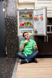 Young Man Sitting In Front Of Fridge Stock Photography