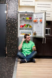 Young Man Sitting In Front Of Fridge Royalty Free Stock Photo