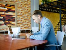 Young man sitting in front of his laptop with a cup of coffee. stock photography