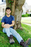 Young man sitting in front yard. A young blue collar worker in jeans, t-shirt and work boots sitting in a front yard under a tree Royalty Free Stock Photography