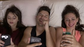 Man sitting between girls laughing and relaxing in the bed making funny faces and playing on their smartphone. Young man sitting between girls laughing and stock video