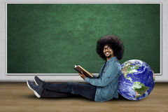 Young man sitting with globe and book. Young man sitting with a globe while holding a book and smiling at the camera in classroom Stock Images