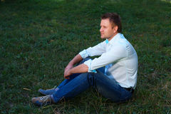 Young man sitting on the grass Royalty Free Stock Image