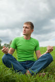 Young man sitting on the grass Royalty Free Stock Images