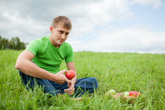 Young man sitting on the grass with apple Stock Image