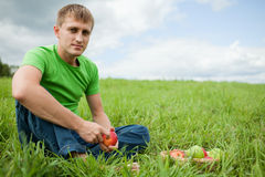 Young man sitting on the grass with apple Stock Photos