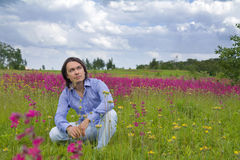 Young man sitting in green meadow Royalty Free Stock Photo