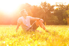 A young man sitting in the Grass Royalty Free Stock Photography