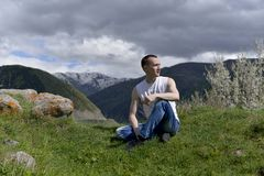 Young man sitting on the grass in the mountains in the warm spring. The sky is overcast, blue clouds gather before the rain stock photo