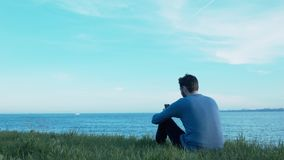 A young man sitting on the grass near the sea writes sms. The boat is passing by, the plane is flying in the sky, a stock video