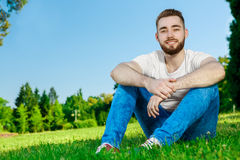 Young man sitting on the grass in park Royalty Free Stock Photo
