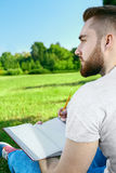 Young man sitting on the grass in park with diary Stock Photo