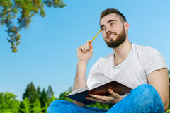 Young man sitting on the grass in park with diary Stock Images