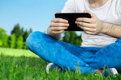 Young man sitting on the grass in park with tablet Royalty Free Stock Image
