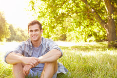 Young man sitting on grass relaxing Stock Image