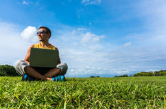 Young man sitting on the grass and working with laptop Stock Images