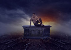 Young man sitting on a grave Stock Photo