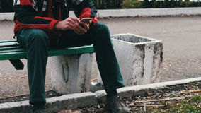 Young man is sitting on a green bench in the park waiting for someone else and typing on a smartphone stock footage