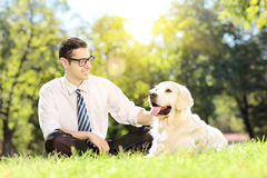 Young man sitting on a green grass next to a dog in a park. Young man sitting on a green grass next to a labrador retriever dog in a park Royalty Free Stock Photos