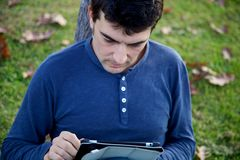 Handsome man working with tablet in park in autumn. Young man sitting on the green grass reading tablet ipad Royalty Free Stock Images