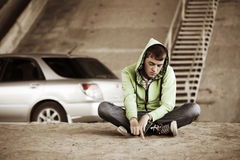 Sad young man sitting on the ground Royalty Free Stock Images