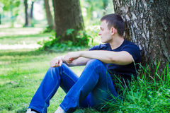Young man sitting on the ground Stock Photography