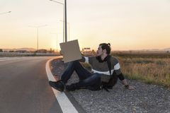 Young man sitting on a ground and hitchhiking Stock Images