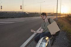 Young man sitting on a guardrail hitchhiking. Selective focus. Sunset time. Back light Royalty Free Stock Photo