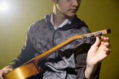 Young man sitting guitar tuning Royalty Free Stock Photography