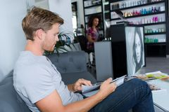 Young man sitting in hairdressers. Man royalty free stock image