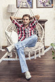 Young man sitting in the hanging chair resting at home Stock Images
