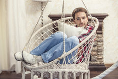 Young man sitting in the hanging chair resting at home Royalty Free Stock Photos