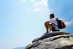 Young man sitting and Having a Rest on top of a mountain Stock Photography
