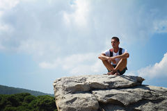 Young man sitting and Having a Rest on top of a mountain Royalty Free Stock Photo
