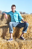 Young Man Sitting on Hay Bales Stock Photos
