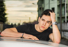 Young man sitting on his car's door, resting on Stock Photos