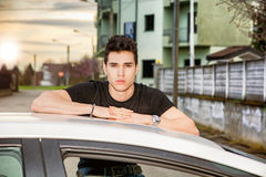 Young man sitting on his car's door, resting on Royalty Free Stock Photos