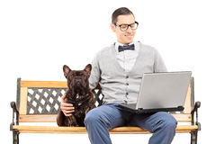 Young man sitting with his dog and working on laptop Royalty Free Stock Image