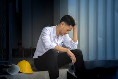 Young engineers fail to make mistakes in their work and business. A young man sitting with his hands close to his face and felt sorry for despair in life Stock Photography