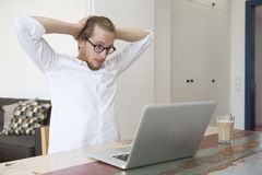 Young man sitting with his laptop and looking stressed and excit Royalty Free Stock Photo
