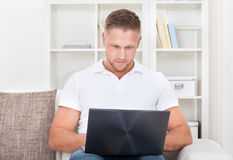 Young man sitting in his living room on the sofa using a laptop Royalty Free Stock Photography