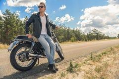 Young man sitting on his motorbike. Enjoying my lifestyle. Biker man wearing leather jacket and sunglasses, sitting on his motorcycle and looking away Royalty Free Stock Photo