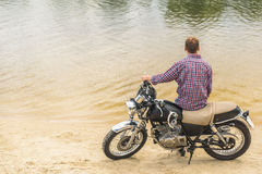 Young man sitting on his motorbike Royalty Free Stock Image