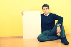 Young man sitting and holding a blank billboard Stock Photo