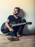 Young man sitting and holding guitar Royalty Free Stock Images