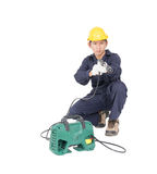 Young man sitting and holding high pressure water gun. Young man in uniform sitting and holding high pressure water gun portable with hose, Cut out isolated on Royalty Free Stock Photo