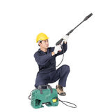 Young man sitting and holding high pressure water gun. Young man in uniform sitting and holding high pressure water gun portable with hose, Cut out isolated on Royalty Free Stock Image