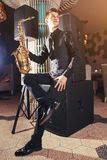 Young man sitting and holding saxophone Royalty Free Stock Images