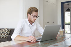 Young man sitting at home looking at his laptop Royalty Free Stock Photo