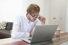 Young man sitting at home looking at his laptop Stock Photography